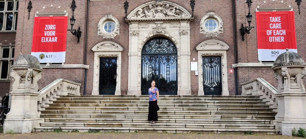 """Elyzabeth on the steps of Royalt Tropical Institute, flanked by the banners """"Zorg voor elkaar"""" and """"Take care of each other"""""""