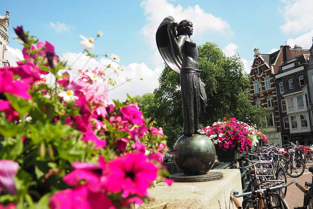 Statue of Fortuna, with pink flowers in the foreground and Amsterdam houses in the background