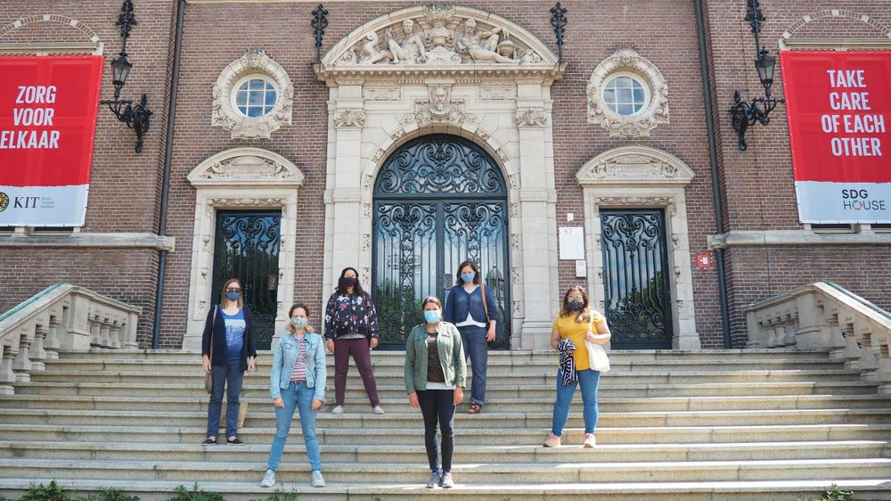 """A Tour group on the steps of Royalt Tropical Institute, flanked by the banners """"Zorg voor elkaar"""" and """"Take care of each other"""""""