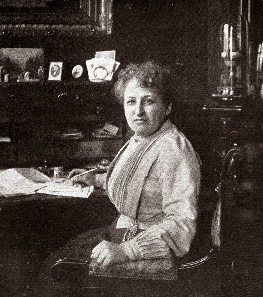 Black & white photo of Aletta Jacobs sitting at her writing desk