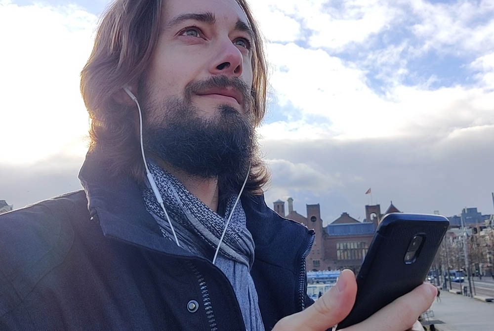 Person holding his phone on the streets of Amsterdam, listening to a hidden history story